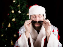 El mún rastoman Santa Claus se sostiene alrededor de los vidrios y de las sonrisas, en el fondo del árbol de navidad diversas emo Imágenes de archivo libres de regalías
