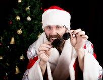 El mún rastoman Santa Claus se sostiene alrededor de los vidrios y de las sonrisas, en el fondo del árbol de navidad diversas emo Fotografía de archivo