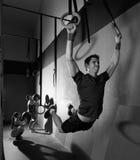 El músculo sube entrenamiento de balanceo del hombre de los anillos en el gimnasio Fotografía de archivo libre de regalías