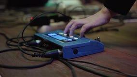 El músico ajusta el procesador de la guitarra antes del funcionamiento presiona el botón en la CPU almacen de video