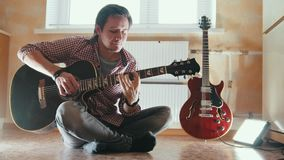 El músico atractivo joven toca la guitarra que se sienta en el piso en la cocina