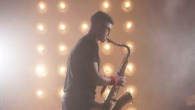 El músico atractivo joven toca el saxofón del tenor en etapa almacen de metraje de vídeo