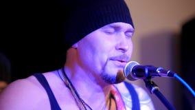 El músico brutal canta en micrófono en el concierto de rock metrajes