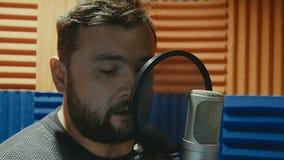 El músico creativo del hombre en el estudio trabaja jugando, cantando y registrando almacen de metraje de vídeo
