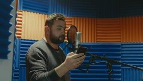 El músico creativo del hombre en el estudio trabaja jugando, cantando y registrando metrajes