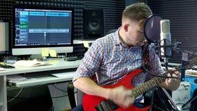 El músico creativo del hombre en el estudio trabaja tocando, cantando y registrando la guitarra con el cuaderno y el micrófono in almacen de video