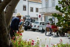 El músico de la calle con el sombrero juega la música de jazz para los turistas - escena de la calle fotografía de archivo