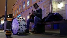 El músico de la calle en el centro de Moscú canta y juega la guitarra y los tambores metrajes