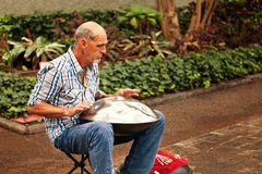El músico de la calle que tocaba un instrumento tradicional llamó caída Foto de archivo libre de regalías