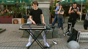 El músico de la calle toca un instrumento musical electrónico
