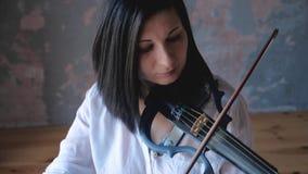 El músico de la mujer se realiza con un electro-violín moderno metrajes