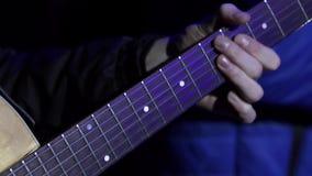 El músico de sexo masculino vestido en equipo negro toca la guitarra acústica en etapa metrajes