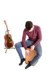 El músico del hombre del adolescente se sienta en un cajon y un juego con una guitarra en b Fotos de archivo libres de regalías