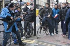 El músico divertido extraño canta delante de adolescentes en la esquina del carril del ladrillo Fotos de archivo