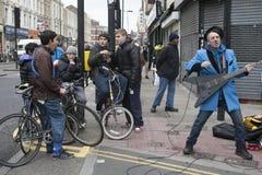 El músico divertido extraño canta delante de adolescentes en la esquina del carril del ladrillo Imagen de archivo libre de regalías
