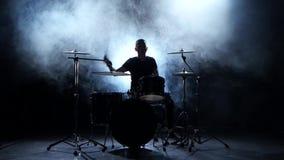 El músico enérgico juega buena música en los tambores Fondo ahumado negro Silueta almacen de metraje de vídeo