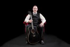 El músico en chaleco y el lazo que se sienta en terciopelo rojo presiden sostener la guitarra Imagen de archivo