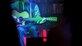 El músico en concierto toca la guitarra acústica almacen de video
