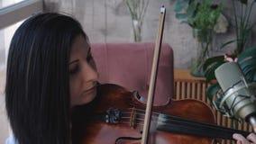 El músico hermoso de la mujer en la camisa blanca toca el violín almacen de metraje de vídeo