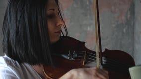 El músico hermoso de la mujer en la camisa blanca toca el violín almacen de video