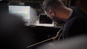 El músico joven del principio está componiendo el musicon una guitarra, sentándose en un estudio de grabación vacío, visión trase almacen de video
