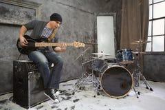 El músico joven toca la guitarra eléctrica baja que se sienta en el amplificador Imagen de archivo libre de regalías