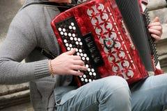 El músico juega el bayan en la calle de la ciudad Fotos de archivo