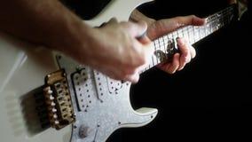 El músico juega un ritmo en una guitarra eléctrica blanca en un fondo negro El hombre está jugando la roca almacen de metraje de vídeo