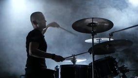 El músico juega una melodía en los tambores Fondo negro del humo Vista lateral siluetas metrajes