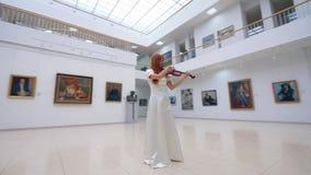 El músico profesional en el vestido blanco toca el violín en museo con las pinturas almacen de video