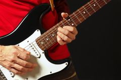 El músico puso los fingeres para los acordes en la guitarra eléctrica en fondo negro Imagenes de archivo