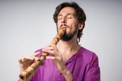 El músico que toca los instrumentos étnicos Hombre que toca la flauta japonesa Imagen de archivo libre de regalías