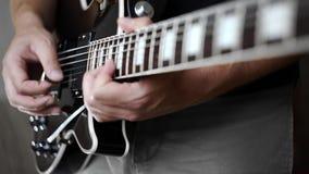 El músico soloing en la guitarra eléctrica, jugando en los instrumentos musicales eléctricos, jugando ruidosamente en la guitarra almacen de metraje de vídeo