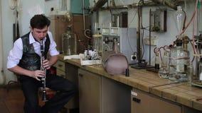 El músico toca la flauta en un laboratorio de química almacen de video
