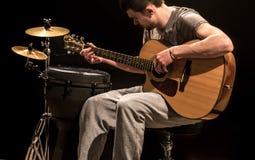El músico toca la guitarra acústica y los instrumentoes de percusión, fondo negro imágenes de archivo libres de regalías