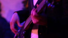 El músico toca la guitarra baja en discolights Manos en el fingerboard almacen de video