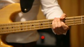 El músico toca la guitarra baja Manos en el fingerboard metrajes