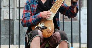 El músico toca un instrumento musical multi-atado metrajes