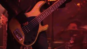 El músico vestido en chaqueta de cuero negra toca la guitarra baja en etapa en el concierto almacen de video