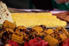 El maíz asado a la parrilla asó a la parrilla en el fuego con la pimienta roja imágenes de archivo libres de regalías