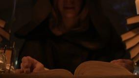 El mago de la muchacha del primer en la capilla en un cuarto oscuro por luz de una vela lee un encanto Cámara viva oscura místico metrajes