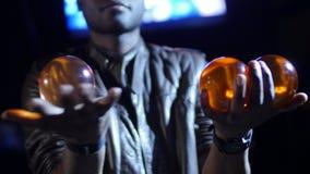 el mago del negro 4K rueda dos bolas rojas en su mano y tercera que él se sostiene en la otra mano almacen de metraje de vídeo