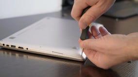 El mago utiliza un destornillador para desatornillar el tornillo de la cubierta del ordenador portátil Reparación de la computado almacen de metraje de vídeo