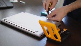 El mago utiliza un destornillador para desatornillar el tornillo de la cubierta del ordenador portátil Reparación de la computado metrajes