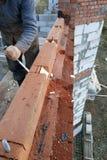 El mago utiliza un pedazo para moler la madera en el edificio foto de archivo