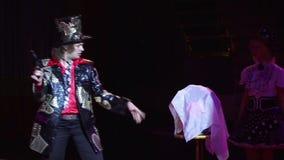 El mago y el ayudante están participando en la demostración El ilusionista tira un arma en un ramo de la flor desaparece almacen de video