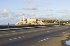 El Malecon and Castillo de los Tres Reyes del Morro Havana Cuba. Havana/Cuba - 30 November 2015 - people on the Malecon  looking at the Castillo de los Tres Stock Photography
