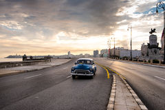 El Malecon famous sea fron promenade in Havana, Cuba. Havana, Cuba - September 22, 2015: Classic american car drive on Havana most popular sea fron promenade, El Royalty Free Stock Photos