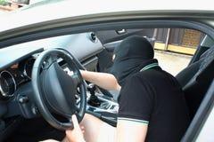 El malhechor en la máscara que roba el coche imagen de archivo