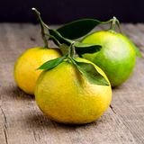 El mandarín maduro con la fruta cítrica del mandarín de la mandarina de las hojas en los agrios de madera del fondo de la tabla c Imagen de archivo